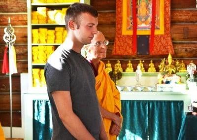 A man looking down, standing beside buddhist nun Venerable Semkye.