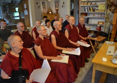 Buddhist nuns, anagarikas and participants siting on chairs and have papers in their hands to take notes as they listen to a teaching