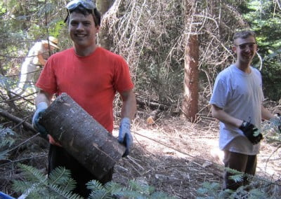 A man wearing gloves and carrying a big log in his hands while another man smiles at the camera.