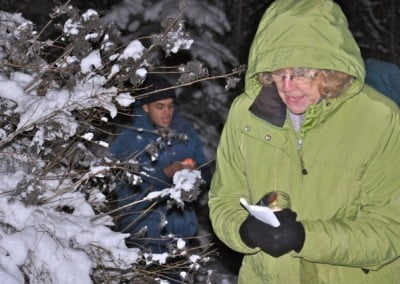 A woman and anagarika, Jack walking past a tree covered with snow, they are holding candles and a piece of paper in their hands.