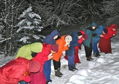 Buddhist nuns, anagarikas, men and women standing in a row and bowing, grounds and trees are covered in snow.