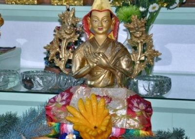 """A very unusual yellow fruit aptly named """"Buddha's hand"""" placed in front of Lama Tsongkhapa statue."""