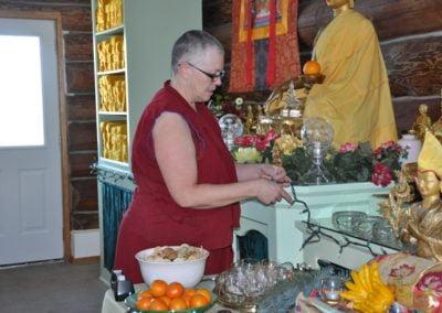 Buddhist nun, Venerable Yeshe putting string lights around the altar.