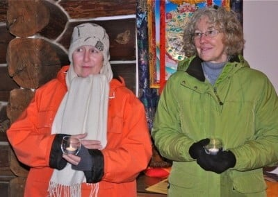 Two women each holding a candle in the Meditation Hall
