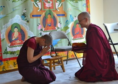 A theravada nun kneeling and bowing at Venerable Tarpa who is also kneeling, taking an offering in her hands.