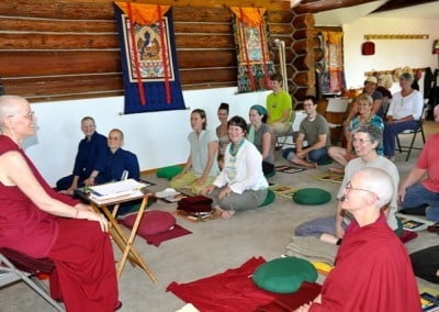 Buddhist nun, Venerable Tarpa sitting on a chair while other lay people sitting on the floor listening.