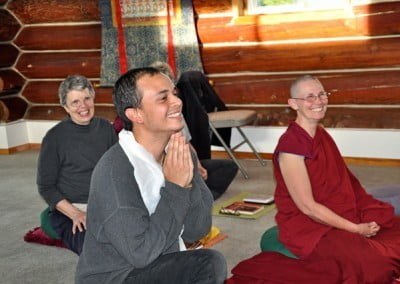 A man in praying gesture smiling happily, sitting beside a buddhist nun.