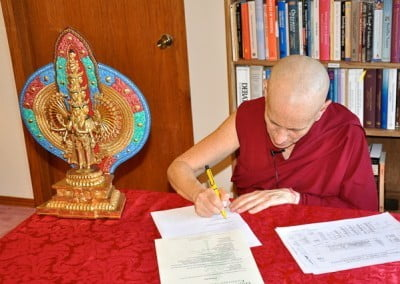 Buddhist nun, Venerable Chodron signing on papers on table, beside a statue of a thousand arm Chenrezig.