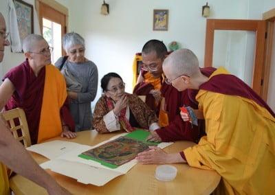 Dagmo-la, Ven. Migmar and buddhist nuns looking at a very old Tara thangka.