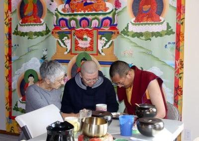 Buddhist monk Ven. Migmar, anagarika Katya and a woman sitting down and looking at something.