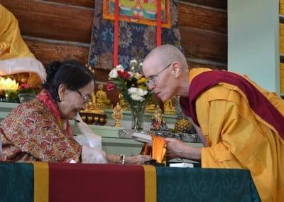 Buddhist nun Venerable Tarpa bending her body and offering a Tara tsatsa to Dagmo-la.