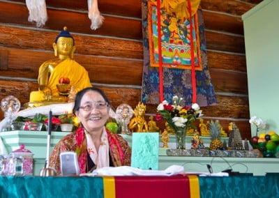 A smiling Dagmo Kusho-la sitting in front of the Buddha statue.