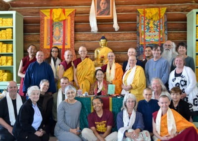 A group photo of Dagmo-la with abbey sangha, anagarikas and retreatants posing with the Buddha.