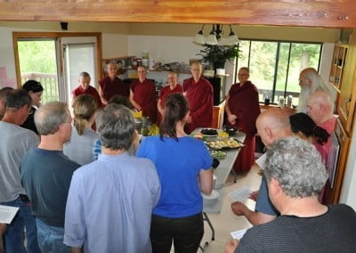 Abbey sangha standing behind a table full of food, while the participants do food offering