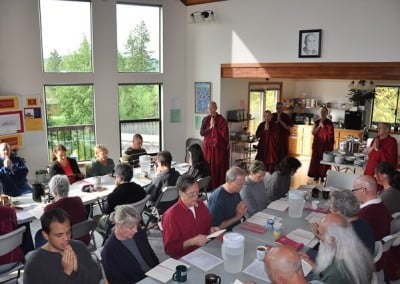 Abbey sangha standing and saying prayers in a room crowned with retreatants sitting down saying prayers togethers.