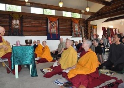 Venerable Chodron sitting on chair giving dharma talks while buddhist nuns and retreatants sitting on the floor listening.