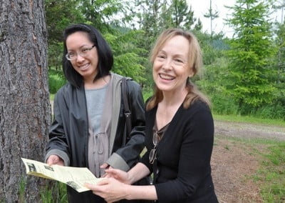 Two women holding a piece of paper together.