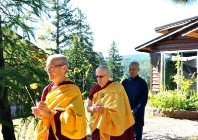 Venerables Semkye and Jigme lead Hsiao Yin from the Meditation Hall.