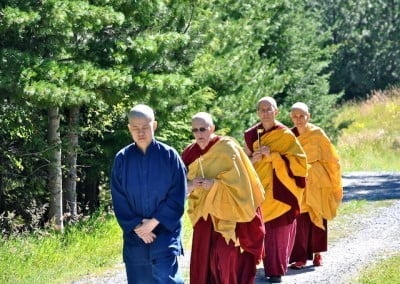 Venerable Chodron follows behind Hsiao Yin, Venerable Jigme, and Venerable Semkye as they walk up the path to the Meditation Hall for the ceremony.