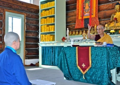 Venerable Chodron sits at the teaching table across from Hsiao Yin, the new Anagarika, and tosses flower petals for auspiciousness.