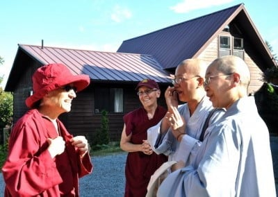Venerables Chodron and Semkye greet two guest nuns in front of Ananda Hall.