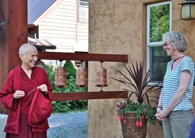 Susan speaks with Venerable Chodron in front of the prayer wheels just outside Chenrezig Hall.