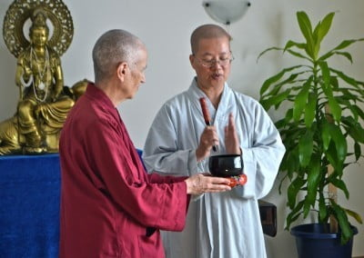 Venerable Chodron holds the bell while Jenkir demonstrates.