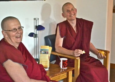 Venerables Jigme and Tsepal sit just outside the dining room and relax after the session.