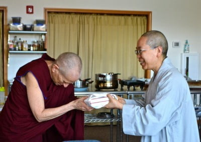 Venerable Chodron offers a gift to Venerable Jendy on behalf of the Abbey.