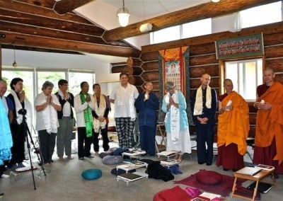 A joyous group of visitors and residents stand in the meditation hall, having made offerings to Venerable Chodron.