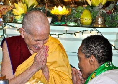 Venerable Chodron and Cheryl bow to each other in front of the altar after Cheryl makes an offering.