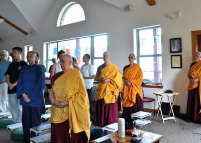 Monastics and guests stand in Chenrezig Hall, awaiting Venerable Chodron and the evening's teachings.