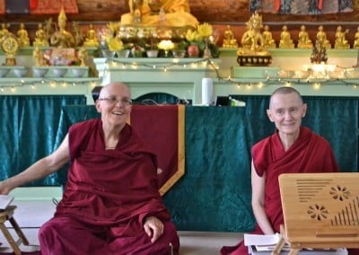 Venerables Semkye and Samten sit in the front of the meditation hall, answering guests' questions.