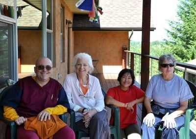 Jamyang, Kathy, Kuni, and Marga pose for a photo on the deck of Chenrezig Hall.