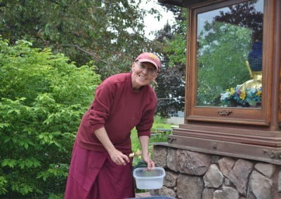 Buddhist nun, Venerable Semkye bending her body taking a brush in one hand and a plastic container in her other hand.