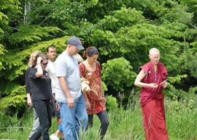 Buddhist nun, Venerable Tarpa walking through the grasses with a group of men and women.