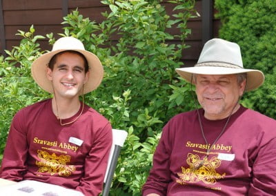 Two men wearing Sravasti Abbey long sleeves shirts sitting on the chairs.