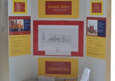 A board with pieces of paper pasted on it introducing the Chenrezig Hall.