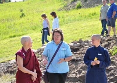 A women wearing a blue shirt talking to Buddhist nun, Semkye and anagarika, Dani.