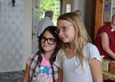 Two young girls wearing glasses and smiling together.