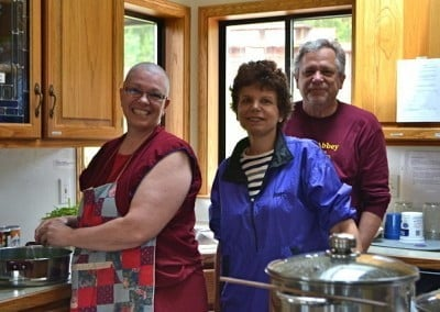 Buddhist nun, Yeshe, a woman and a man standing in the kitchen posing.