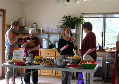 Four women standing and talking beside a table full of food.