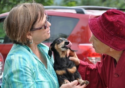 Ven. Chodron greets a little dachshund and her owner.