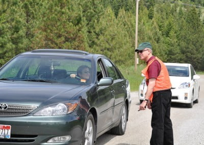 A volunteer standing beside a car, directs the visitors to the parking areas.