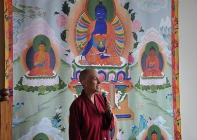 Venerable Chodron holding a mike, behind her is a large thangka of Medicine Buddha.