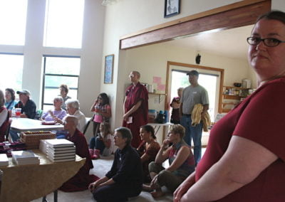 Lay people, some sitting and some standing, listening to Venerable Chodron