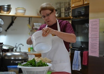 A woman wearing an apron, helping in the kitchen.