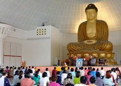 Venerable Chodron giving a dharma talk to a large numbers of people in a big hall, behind her is an enormous statue of Shakyamuni Buddha.
