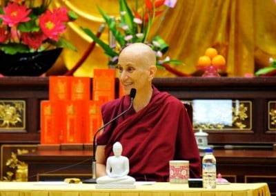 A close up photo of Venerable Chodron giving dharma talk, on the table there is a white statue of Shakyamuni Buddha.
