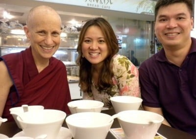 Venerable Chodron posing with a woman and a man, several white bowls on the table.